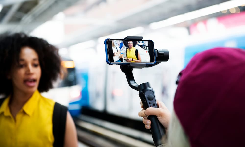 Smartphone filming video of person wearing backpack