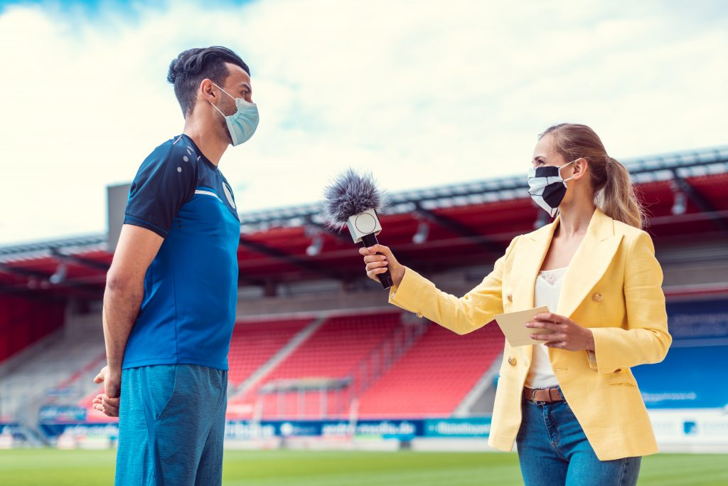 A sports analyst trained by Be On Air conducts a player interview on the field