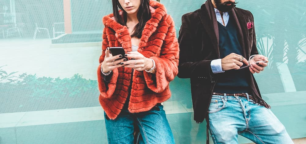 Two young adults stand outside texting in cold weather as M&S Media explain marketing techniques for business owners during the holidays