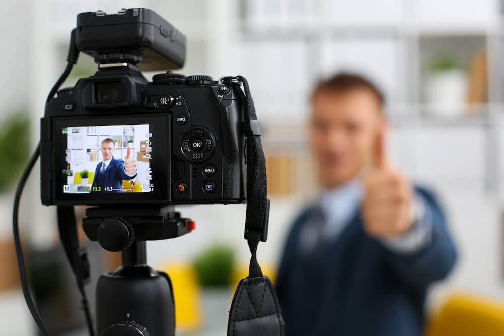 A young man in a suit and tie films himself creating a video resume for employment opportunities