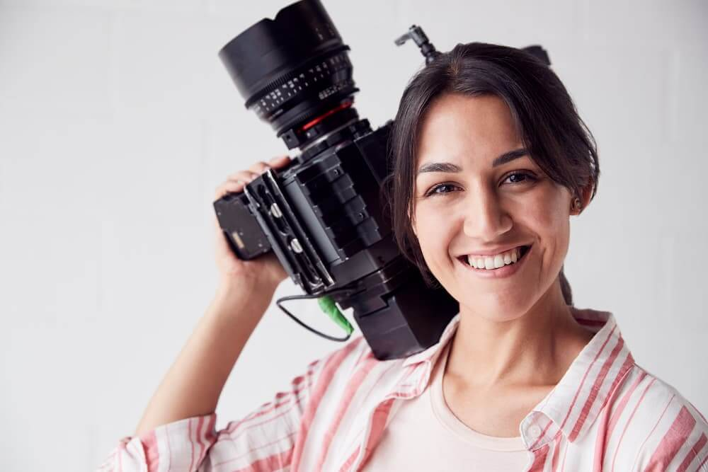 A young woman holds a digital camera as she readies herself to begin her digital media production path