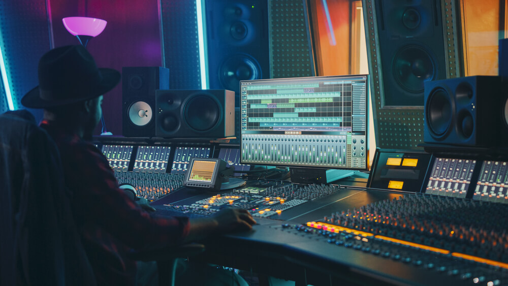 An audio engineer works on a mixing software on his audio console in a dimly lit professional studio