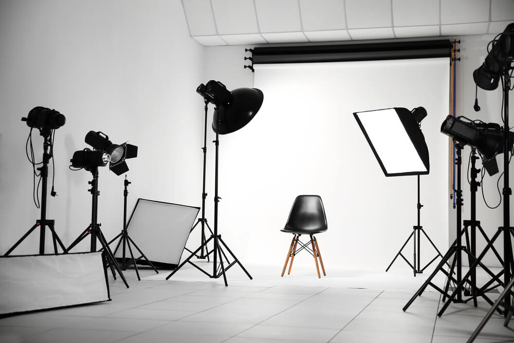 An empty professional photography studio with professional lighting fixtures as M&S Media explains lighting tips for videos