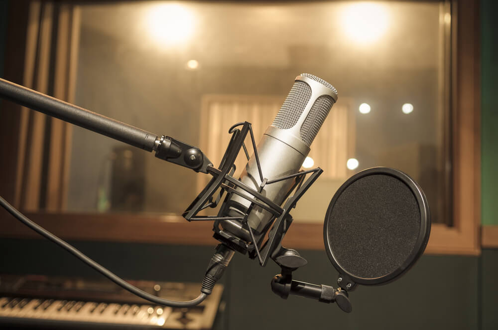 A microphone in a professional recording studio sits idle as Be On Air explains proper microphone set up and usage